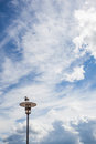 Sea gull sitting on a lamp post in front of cloudy sky but blue Royalty Free Stock Photography
