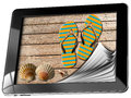 Sea holiday in tablet computer with pages seashells and flip flops sandals on wooden floor sand concept of Stock Photos