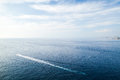 Sea landscape with wake of small fast motorboat mediterranean under blue cloudy sky Royalty Free Stock Image