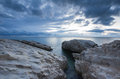 Sea long exposure shot of clouds passing by rocks Royalty Free Stock Images