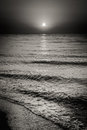 Sea ocean water waves and sun at sunset background black white dramatic landscape with Stock Photos