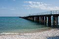 Sea pier long on black beach in koktebel crimea Royalty Free Stock Images