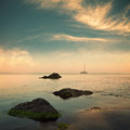 Sea and sailboat on horizon with cloudy sky retro style image colors Royalty Free Stock Photo