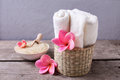 Sea salt in bowl, towels and flowers on  rustic  wooden  backgro Royalty Free Stock Photo
