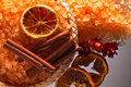 Sea salt with dried oranges and cinnamon sticks on glass table Stock Image