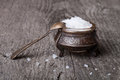 Sea salt in an old utensils and a small spoon on a wooden table Royalty Free Stock Photo