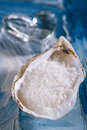 Sea salt in sea shell oyster on blue persian and heart glass abstract painted background Royalty Free Stock Photography