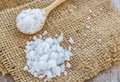 Sea salt in wooden spoon on burlap sack background Royalty Free Stock Photo