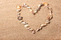 Sea shell heart shape small seashells in the of a on a sandy beach Royalty Free Stock Photo