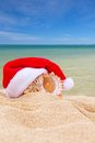 Sea shell in red santa s hat at the beach lying on sand turquoise water and a blue sky background christmas tropical Stock Photography
