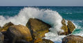 Sea splash wave crushes hot summer rocks Royalty Free Stock Image