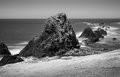 Sea stacks on oreogn coast wide view of oregon with waves washing in against shoreline in black and white Royalty Free Stock Photo