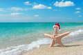 Sea-star in santa hat at sea sandy beach. Holiday concept Royalty Free Stock Photo