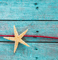 Sea star or starfish with decorative red rope on a background of rustic painted turquoise blue wooden boards nail holes and Royalty Free Stock Image