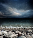 Sea stones waves and dark sky coast dramatic stormy landscape Stock Image