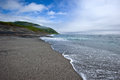 Sea surf on the beach of volcanic sand. Iturup. Royalty Free Stock Images