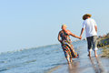 Sea walk happy mature couple at seashore sandy beach and holding hands walking on embracing on summer outdoors background Royalty Free Stock Photo