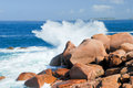 Sea wave breaks against the pink granite rocks Royalty Free Stock Image