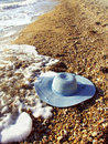Sea and women`s hat on a shingle beach Stock Photo