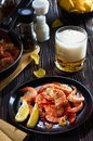 Seafood at the bar, composition of black plate with shrimp lemon beer chips