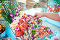 Seafood buffet hand with fork in in hotel restaurant Stock Photos