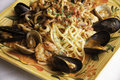 Seafood fra diavolo with linguine a colorful platter holds over fresh littleneck clams mussels shrimp and squid are piled over the Stock Photo