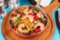 Warm salad of grilled fish pieces, shrimps and mussels in a frying pan Royalty Free Stock Photo