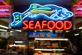 Seafood neon signage near grocery shop at night Stock Images