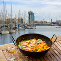 Seafood paella in seaside cafe barcelona with glass of wine port of Royalty Free Stock Image