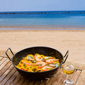 Seafood paella in seaside cafe with glass of wine Royalty Free Stock Photos