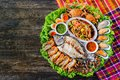 Seafood Somtum has clams shrimp, crabs, boiled eggs, grilled tilapia, placed in a beautifully placed tray on a wooden table