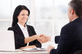 Sealing a deal two cheerful business people handshaking and smiling while sitting face to face at the table Stock Photography