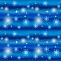 Seamless blue winter background texture with snowflakes and small stars Royalty Free Stock Images