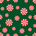 Seamless Christmas pattern with candy on green background.