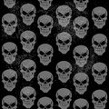 Seamless grunge pattern of gray grinning skulls on black background Stock Photos