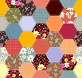 Seamless patchwork pattern from colorful hexagon patches with flowers. Quilting design background