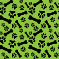 Seamless pattern with black dog paw prints and bones on a green background Royalty Free Stock Photo