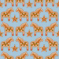Seamless pattern with Christmas gingerbread cookies - Xmas stars and horses on blue background. Royalty Free Stock Photo