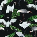 Seamless pattern with cranes and leaves of palm trees