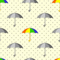 Seamless pattern with grey and colorful umbrellas and raindrops