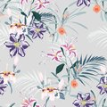 Seamless pattern, light vintage colors palm leaves and pink lilies, clematis and exotic tropical paradise flowers on vintage blue