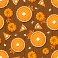 Seamless pattern with pumpkin pies and pumpkins on a wooden background