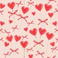 Seamless pattern. Red candy in the shape of heart bandaged with ribbon. Valentine`s gift for St. Valentine`s Day. Vector