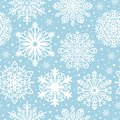 Seamless pattern with white snowflakes on blue background. Winter background for Christmas, Noel, New Year