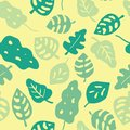 Seamless vector background green leaves. Leaves in shades of green on a yellow background. Hand drawn tropical leaves pattern.