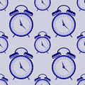 Seamless vector pattern. Symmetrical background with closeup blue alarm clocks on the blue background Royalty Free Stock Photo
