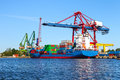 Seaport crane and huge container cargo ship ready for unloading Royalty Free Stock Images