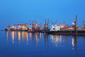 Seaport at night with light reflections on sea water Royalty Free Stock Photo