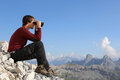 Searching the destination through binoculars in the mountains young man looking Stock Photography
