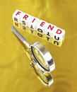 Searching for a friend text in red uppercase letters on small white cubes placed on gold background with hand magnifier indicating Stock Photo